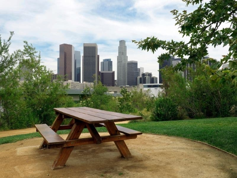 Empty picnic table in Los Angeles city park with a view of the LA skyline in the background on a partly cloudy day.