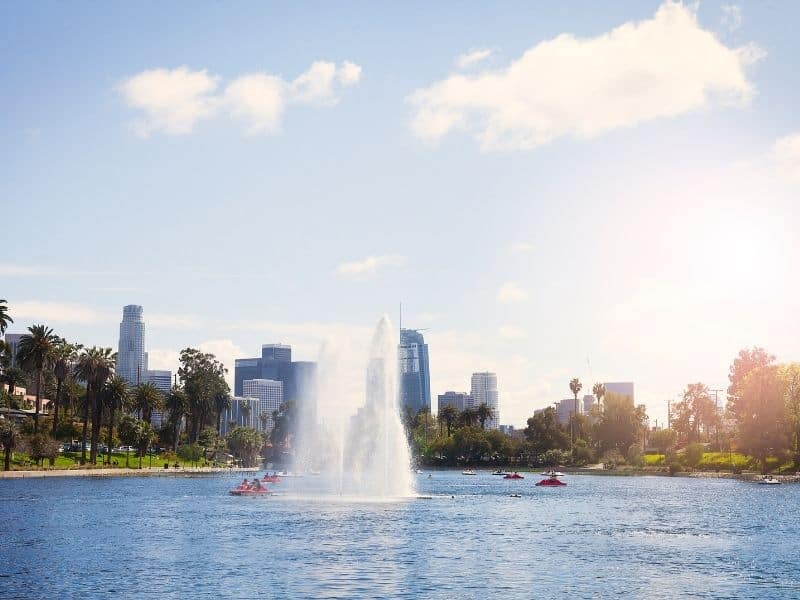 People out enjoying boats on Echo Park Lake in Los Angeles with palm trees and skyscrapers in the background.