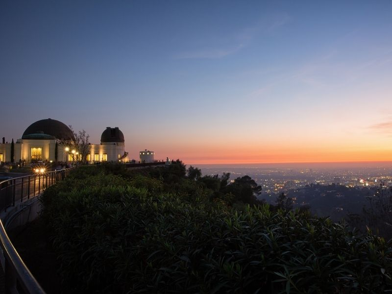 Sunset as seen from the Griffith Park observatory in Los Angeles: observatory lit up on the left side of the photo with the sunset colors and horizon in the distance.