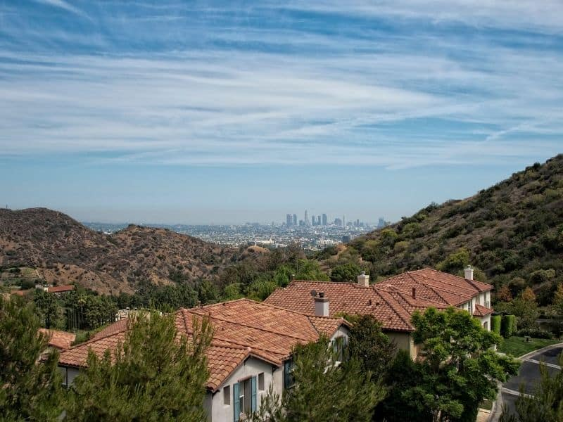 Panorama of Los Angeles as seen from Mulholland Drive: beautiful houses, landscape, and distant cityscape on a sunny day.
