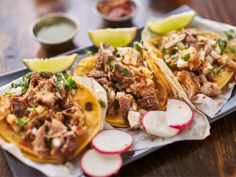 Plate of 3 tasty carnitas tacos with radish and lime and salsas on the side