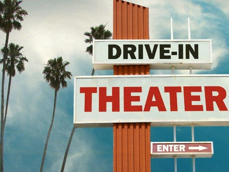 "Cloudy sky with palm trees and text that reads ""Drive in Theater"" and ""Enter"" with an arrow pointing right."