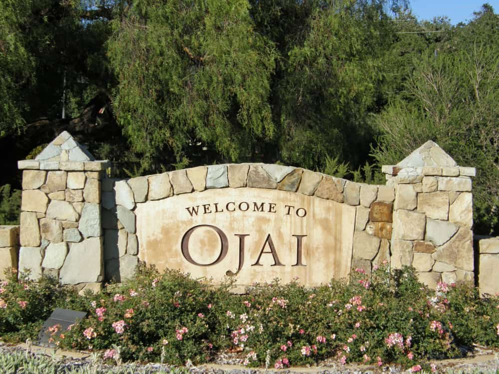 "Stone sign which reads ""Welcome to Ojai"" with flowers and trees behind it."