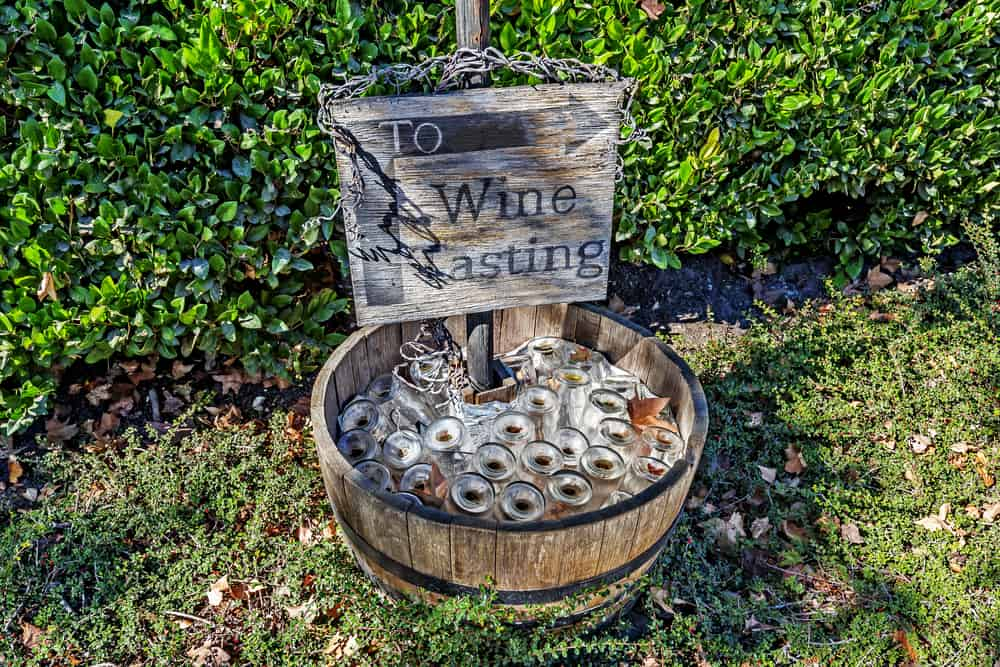 "A sign that says ""To wine tasting"" with an arrow pointing to a wine tasting area in a Santa Barbara winery"