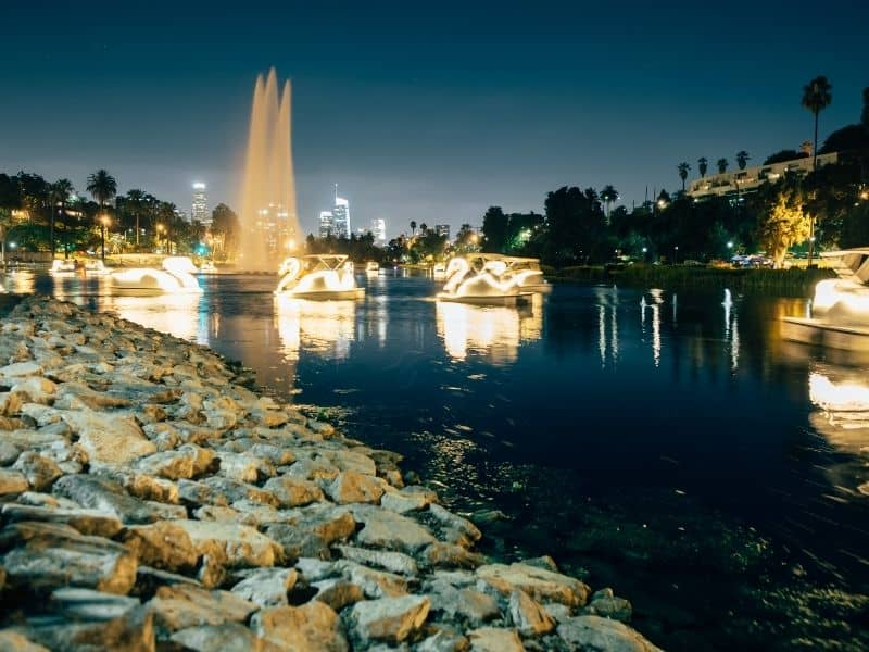 A lake with a tall water fountain jet streaming in the air and several lit-up swan boats after the sunset in Los Angeles.