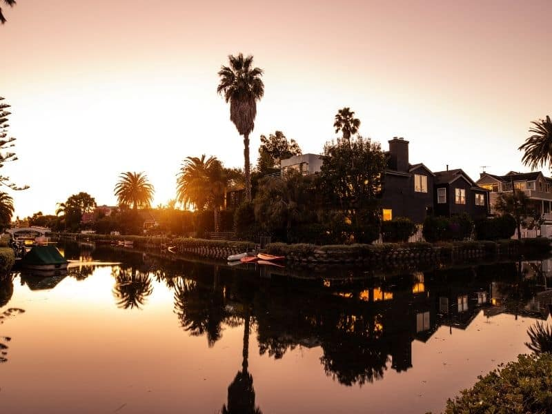 The setting sun over the houses of the Venice Canals, reflecting in the still canal water showing the setting sun and palm trees, a beautiful sunset spot in Los Angeles.
