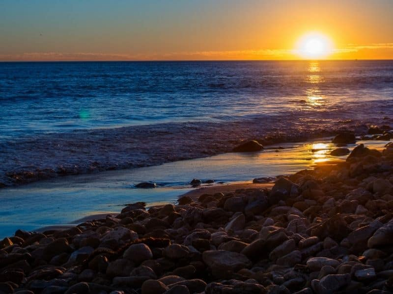 Rocky beach in Malibu, reflecting the setting suns colors in the still ocean.