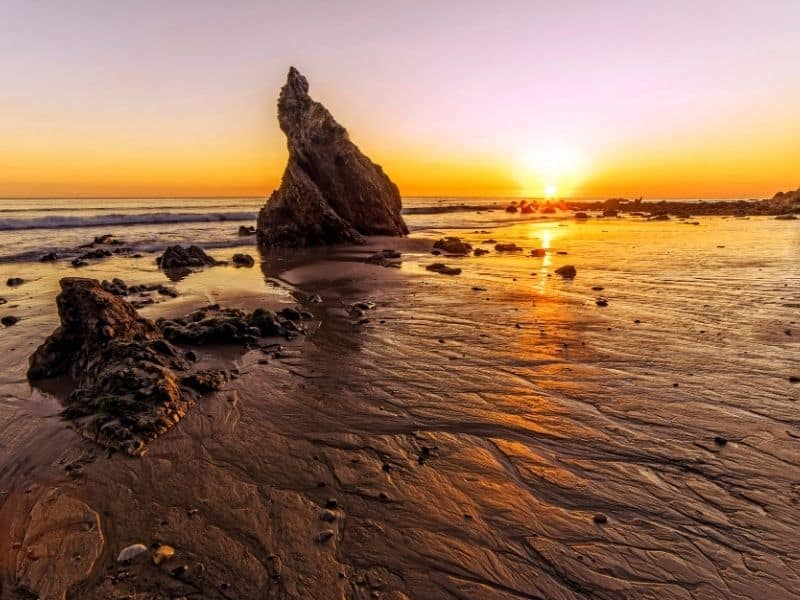 Beautiful sea stacks rising out of the beach with water-rippled sand in the foreground and the setting sun turning the sky orange in the background: easily one of the best places to watch the sunset near Los Angeles