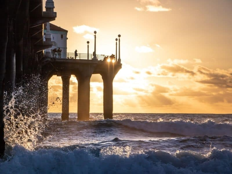 Rough ocean surf crashing against the wooden legs of the Manhattan Beach Pier as the orange sunset sky is alit by the setting sun.