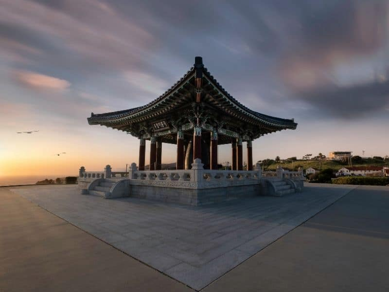 Traditional square Korean pagoda with a flared rooftop, against a backdrop of the ocean, two seagulls, and the colors of the setting sun.
