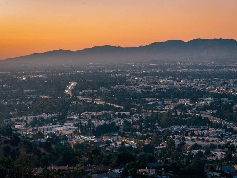 View over the Valley with houses starting to light up and roads beneath the mountain view, with an orange sky at sunset in Los Angeles.