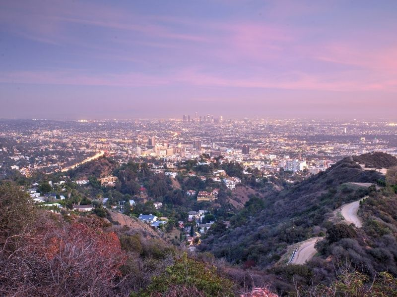 Lavender and pink view of the sunset in Los Angeles, with a hiking trail in the foreground and the city stretching out below, including tall skyscrapers way off in the distance.
