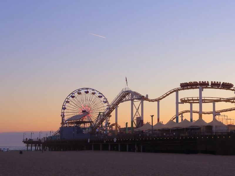 Pastel toned beach sunset in Los Angeles with a view of the roller coaster and Ferris wheel of the Santa Monica pier as well as part of the beach and ocean.