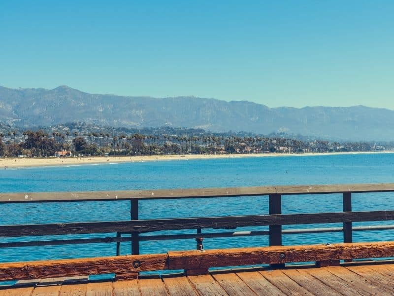 View from the pier of the Santa Barbara wharf, looking onto a clear cerulean beach, with the city in the distance.