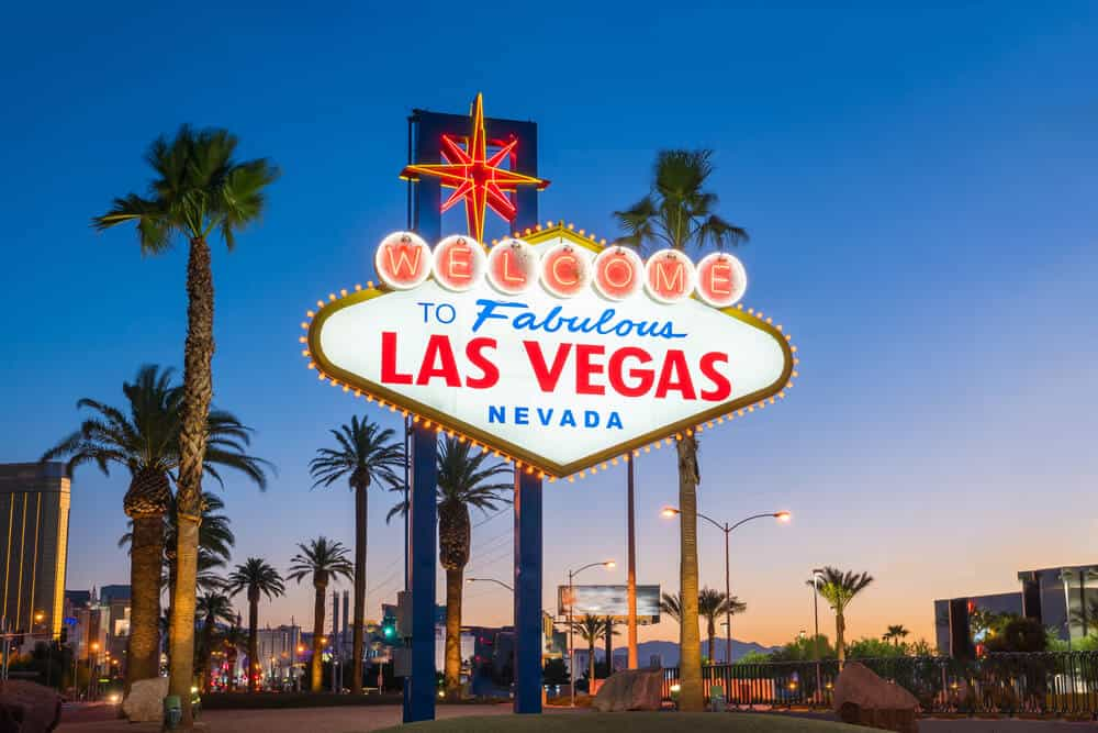 """Famous nostalgic neon sign that reads """"welcome to Fabulous Las Vegas Nevada"""" with palm trees and city lights in the background, just after sunset with orange light on the horizon and a dark blue sky."""