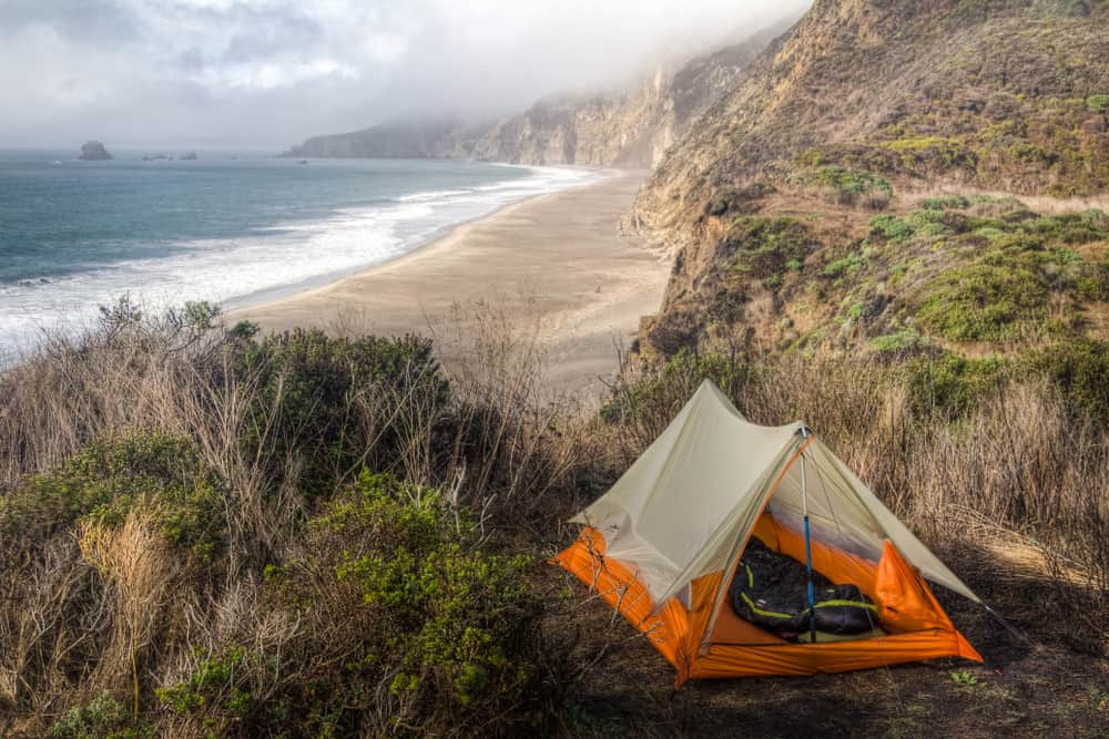 Orange tent perched on a bluff amidst lots of grass, overlooking the beautiful beach below at this Point Reyes campground near San Francisco on a slightly foggy day.
