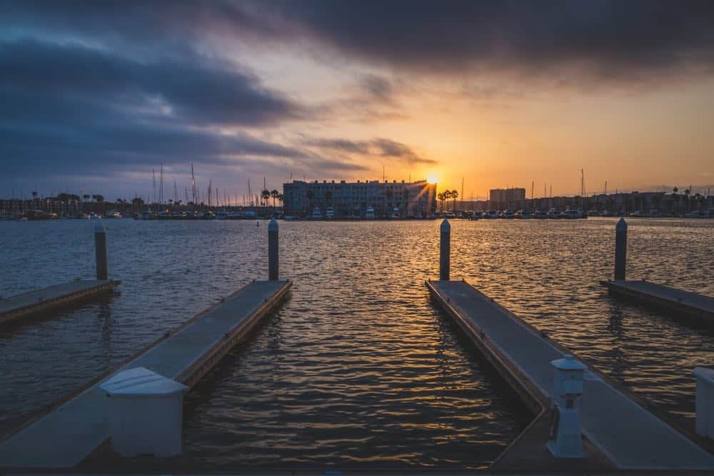 Empty boat docks in the marina with a view of sailboats and the setting sun off in the distance, with the ocean reflecting the setting sun's last rays.