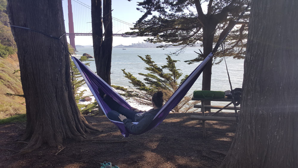 A woman reclining in a hammock with some equipment on a picnic table, overlooking the red Golden Gate Bridge and blue water.