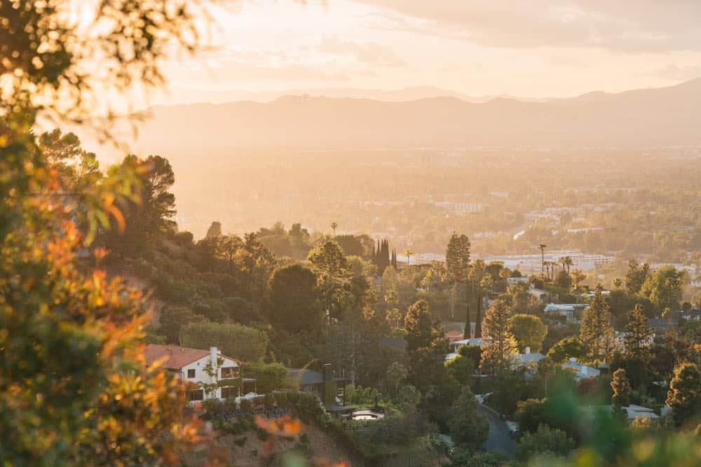 Orange-hued sunset view in Los Angeles of trees and greenery and houses, seen from Mulholland Drive.