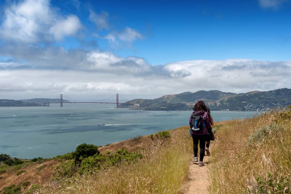 Hikers climbing Mt. Livermore in Angel Island State Park, with views of the Golden Gate Bridge