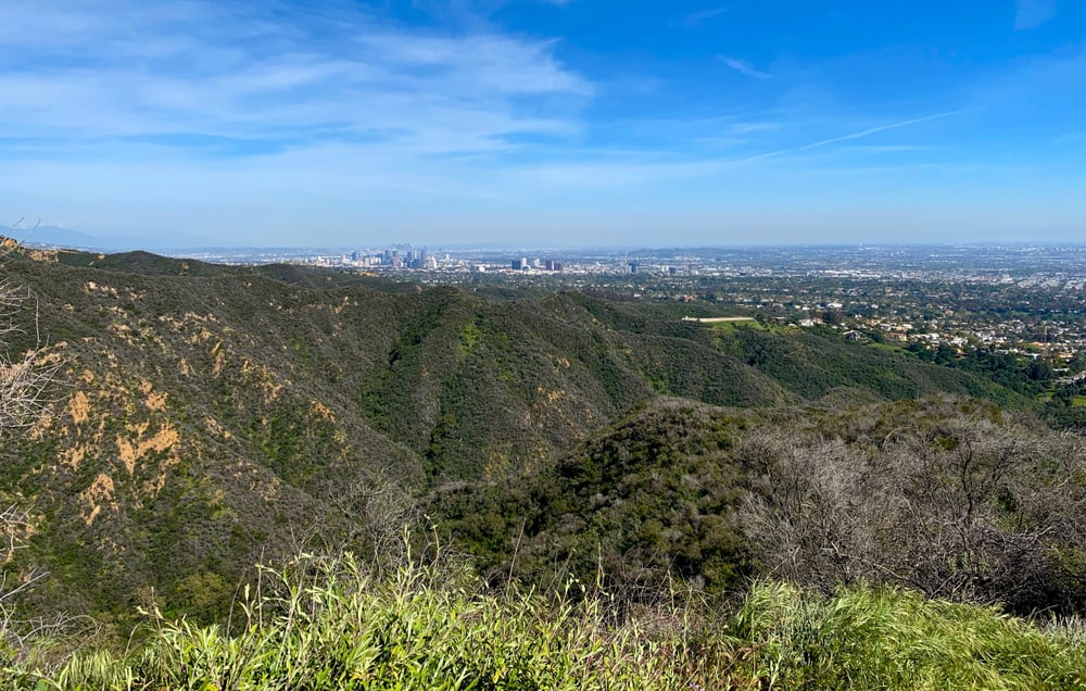 Views of Temescal Canyon, a popular LA hiking destination: green rugged hills with the cityscape small in the distant background on a sunny day.