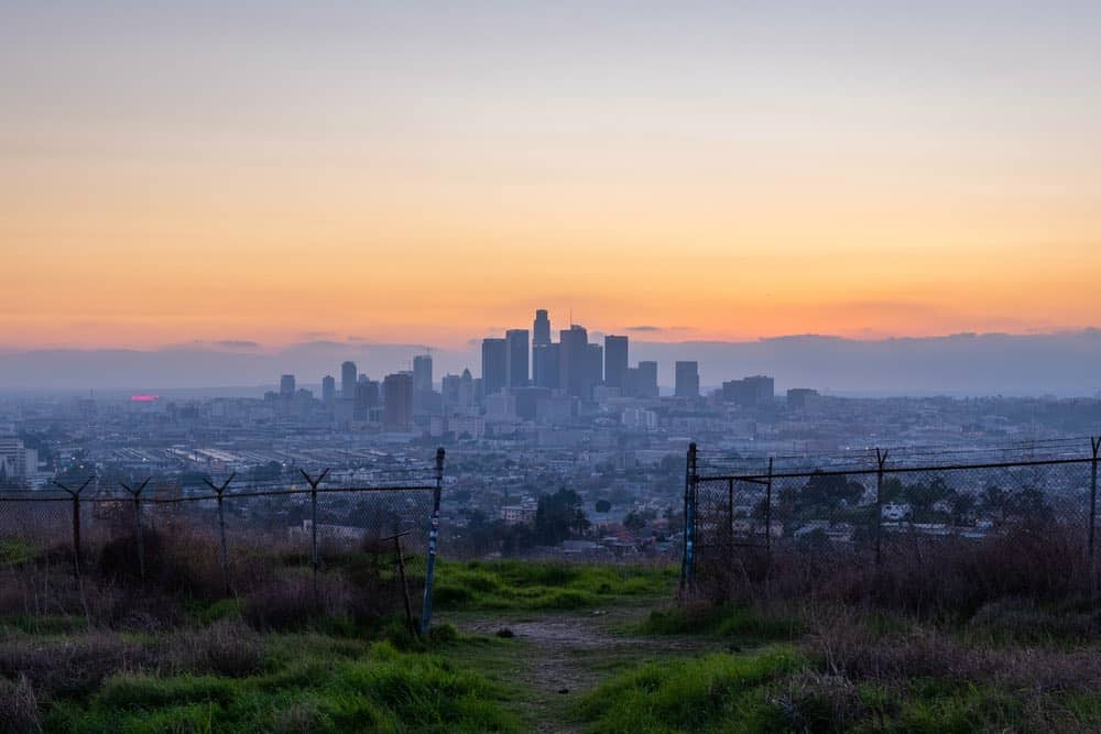 A grassy hill with a gate with an opening in it, drawing the eye to the Los Angeles sunset and skyline, with the sky lit up in purple and orange.