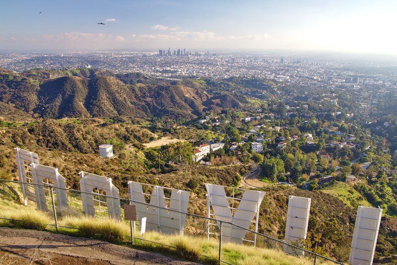 """View of the Hollywood sign letters """"LLYWOOD"""" from the overlook in late afternoon before sunset, with views of the Hollywood hills and sprawling cityscape below."""