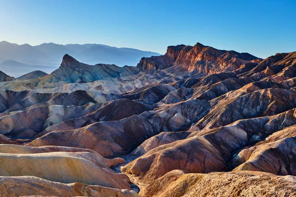 The lunar-looking landscapes of Death Valley National park with red, orange, and purple rippled rocks, on a clear day in the desert.