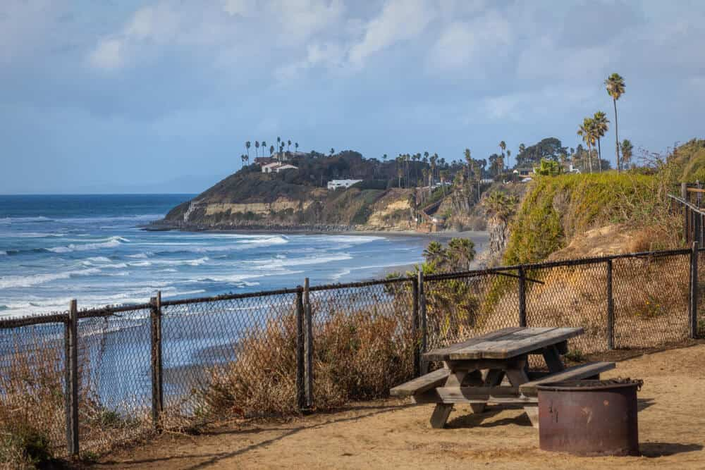 the picnic table at the campsite at san elijo state beach with a view of palm trees, pacific ocean, and swamis cliff