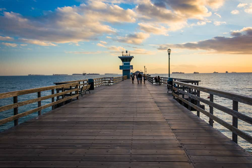 A nearly empty wooden pier at sunset with one small turquoise building and several people walking in a group in the distance, the ocean underneath the pier.