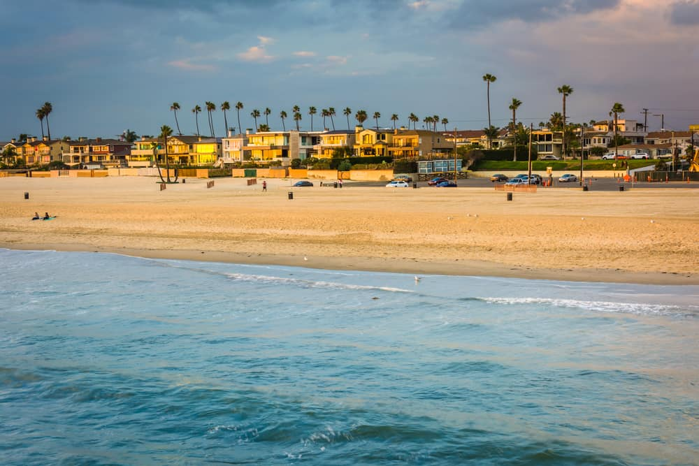 View of Seal Beach town taken from the pier at sunset, so you can see the water, sand, houses, palm trees, and colorful sky at sunset.