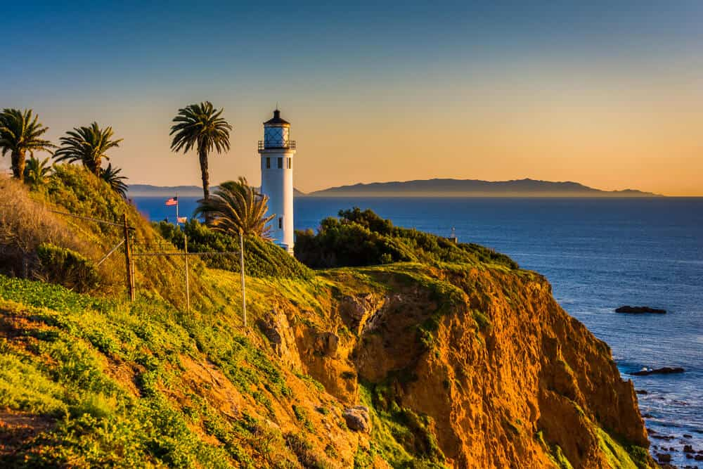 Sunset at the Point Vincente lighthouse, a white lighthouse with a red roof on a cliff in Southern California with four palm trees around it, orange horizon at sunset.