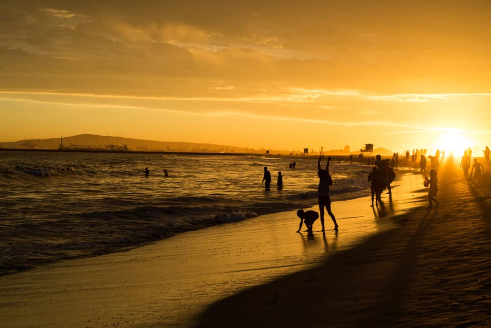 Orange sunset sky with people showing up as black silhouettes playing in the sand and water