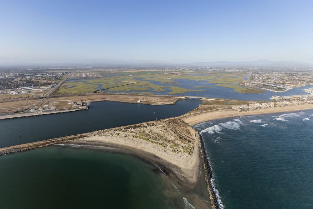 Aerial drone photo of sand meeting the ocean as well as salt marsh (green small islands in a bay) on a sunny day
