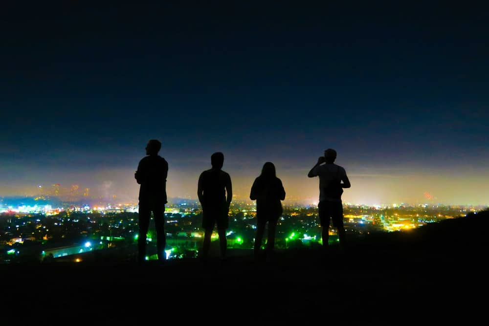 Four silhouettes against a dark sky lit up by the city lights of Los Angeles beneath them.