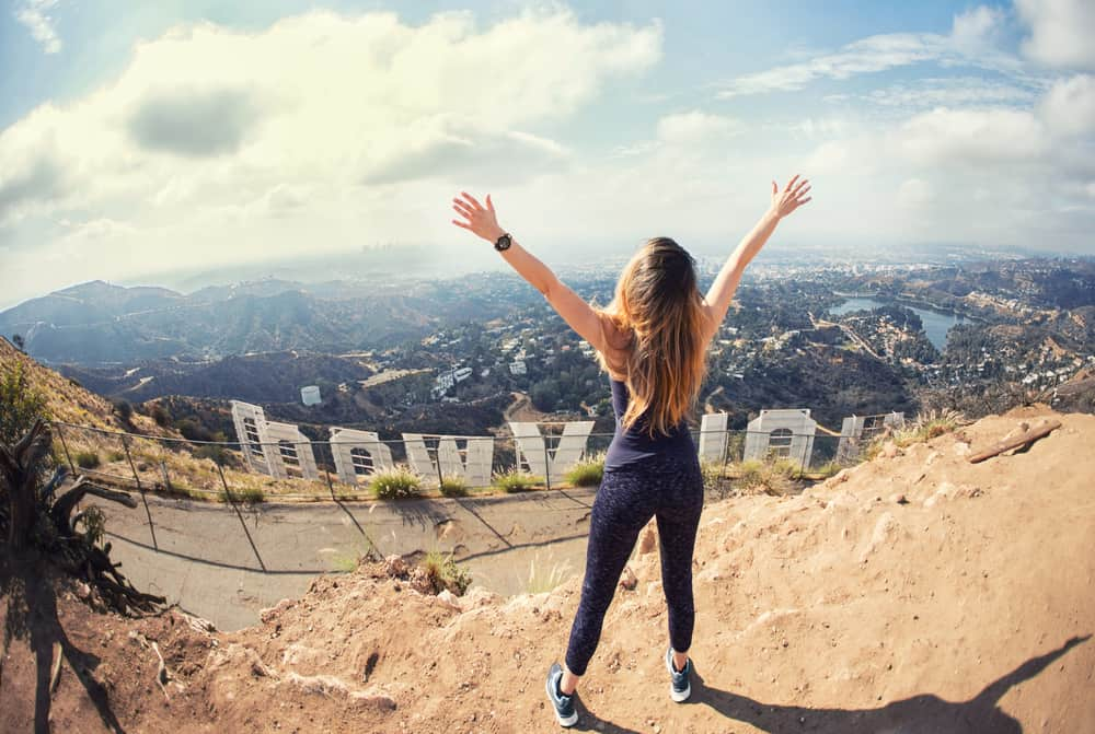 A blond woman in black athletic clothing celebrates reaching the top of the Hollywood sign, with her arms up in the air, the sign below her and the city as well.