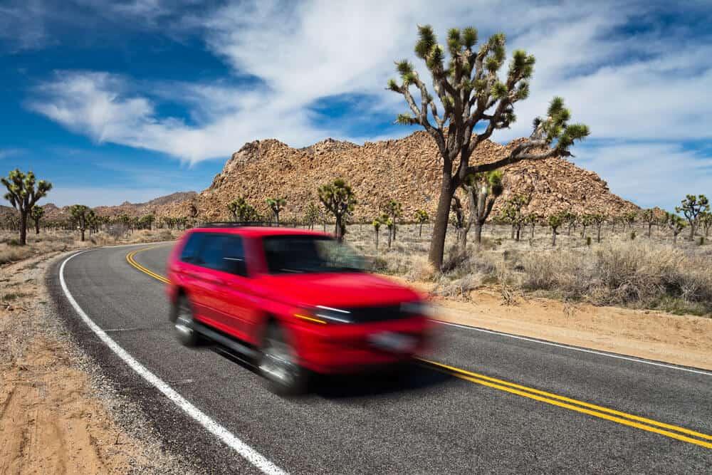 A blurry red car passing through the still desert landscape of Joshua Tree, full of cacti, desert brush, and mountains.