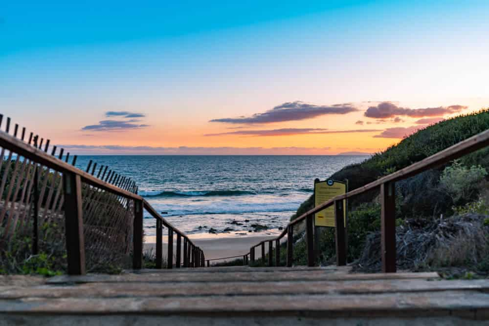 Sunset at a staircase in Crystal Cove State Park leading to the ocean
