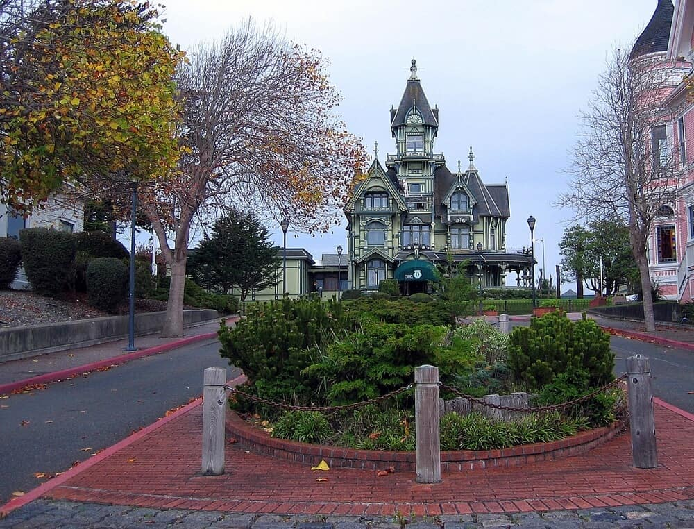 The colorful pale green mansion of Carson Mansion, Victorian architecture classic, surrounded by trees and a small square in Eureka, California