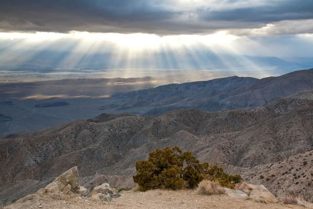 The sun bursting through a dark cloud, scattering rays over the mountainous landscape below, close to sunset at Keys View.