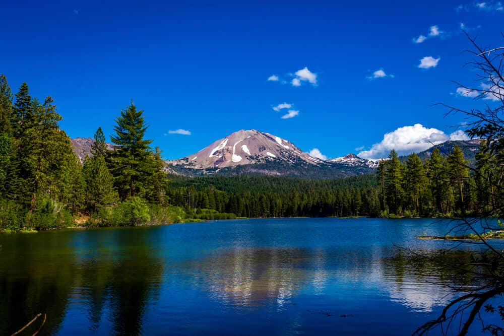 The deep blue waters of Manzanita Lake reflecting the peak of Mt Shasta in the water on a blue sky day with very few clouds