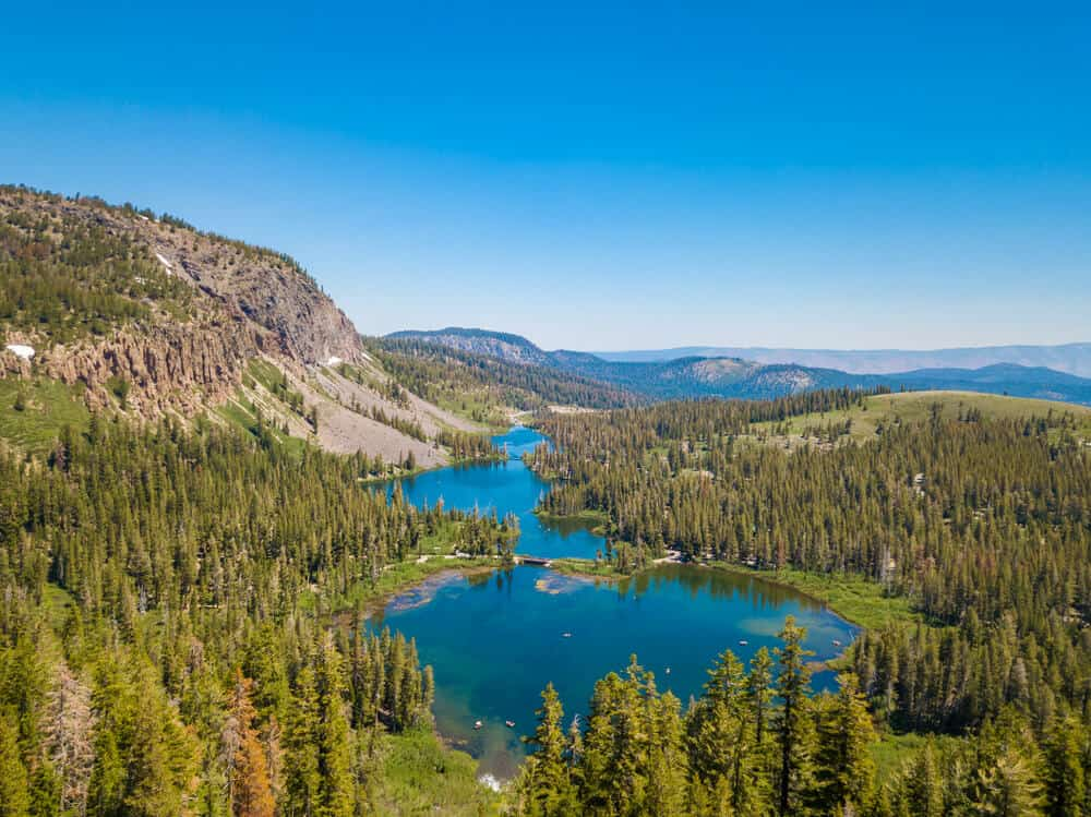 Twin lakes of Mammoth Lakes: two slightly connected brilliant turquoise lakes surrounded by lots of pine trees and low-lying hills and mountains on a sunny day