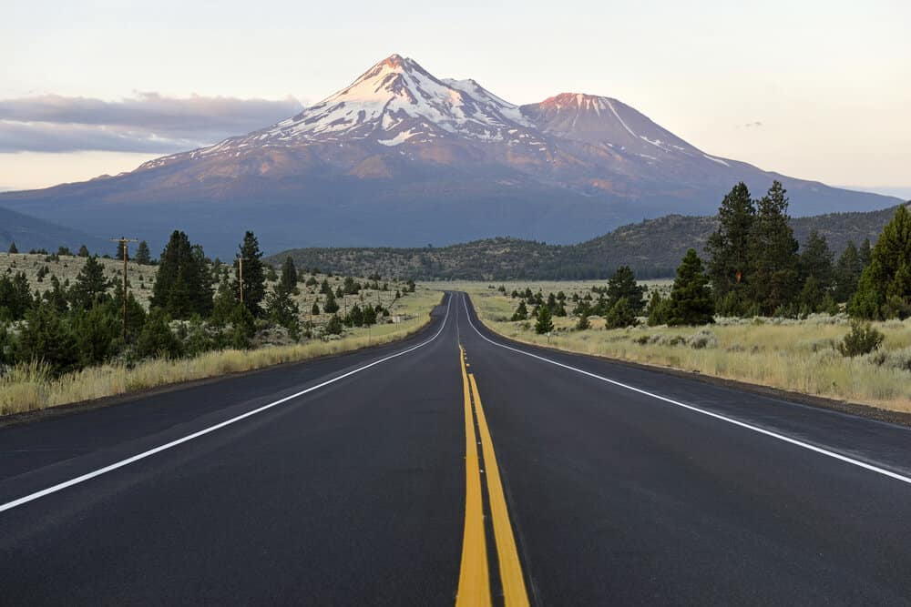 An open road leading towards the tall peak of Mt Shasta, a volcano in California, covered in a bit of snow and covered in sunset light.
