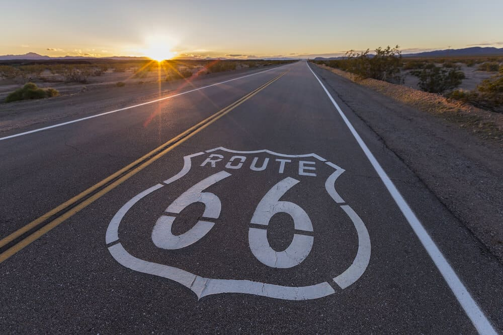 """Road sign painted on the side of the highway lane which reads """"Route 66"""" at sunset with a sunburst as the sun dips below the horizon. Road is empty."""