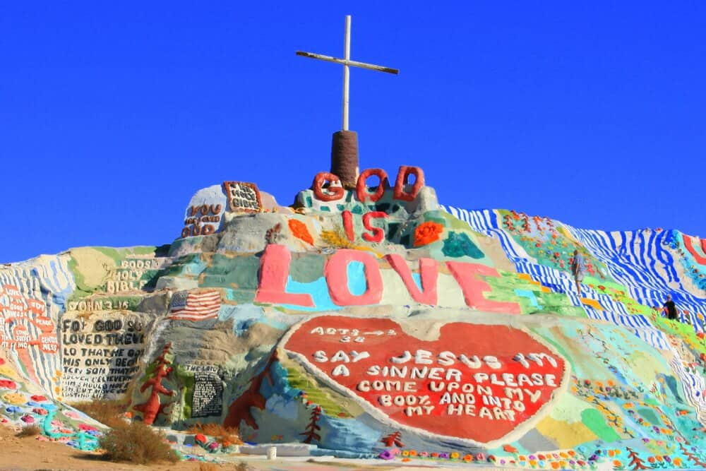 """Colorfully painted rocks in the desert, topped with a cross on top, which reads """"God is love"""" and """"Say Jesus I'm a sinner please come upon my body and into my heart."""""""