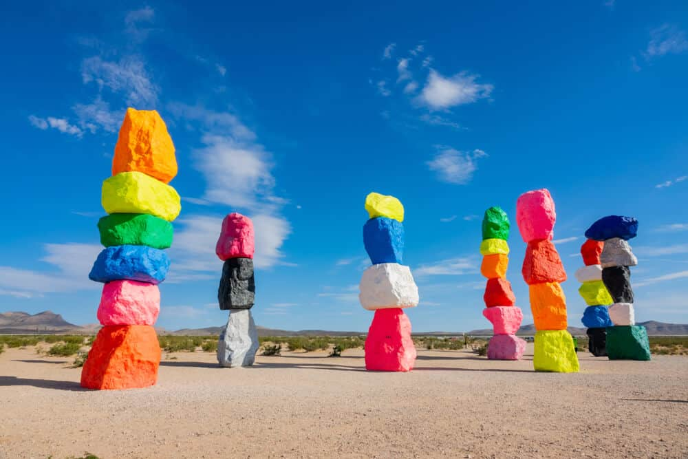 Seven colorful painted stacked rocks in the middle of a desert landscape outside of Las Vegas, a popular road trip stop between LA and Vegas.