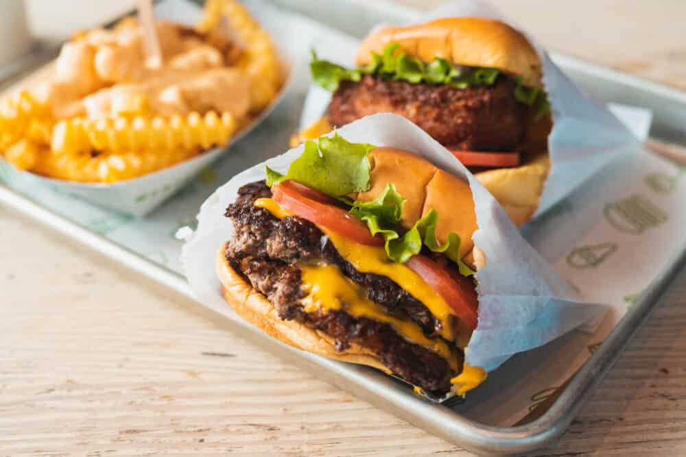 A double cheeseburger and a fried mushroom burger with a side of crinkle cut fries from the burger chain Shake Shack.