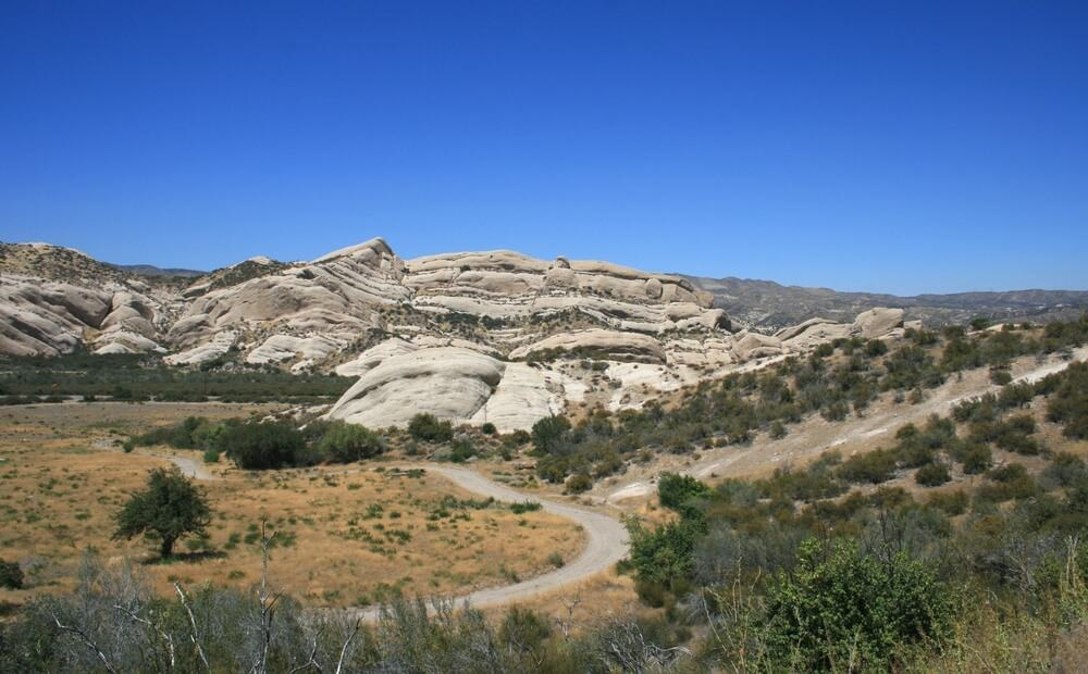Mormon rocks in Phelan, California:  geological formations and a meadow beneath a blue sky on the road trip from Los Angeles to Vegas