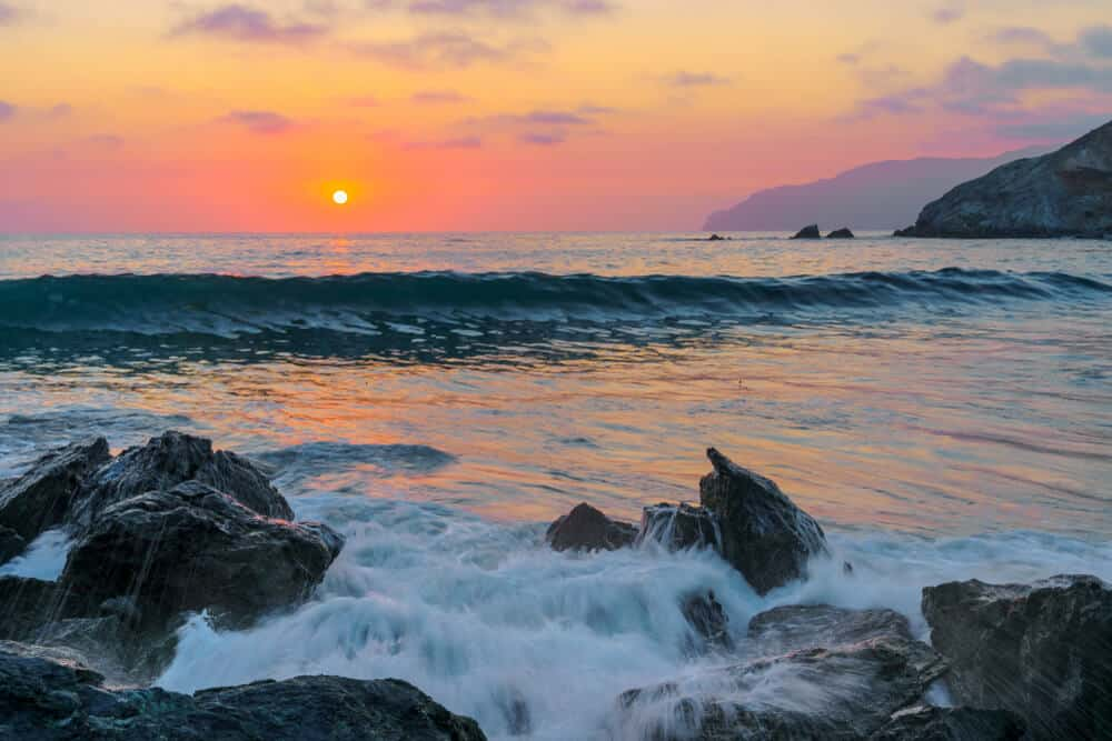 beach on Catalina island at sunset with pink and orange sky and rocks in the water