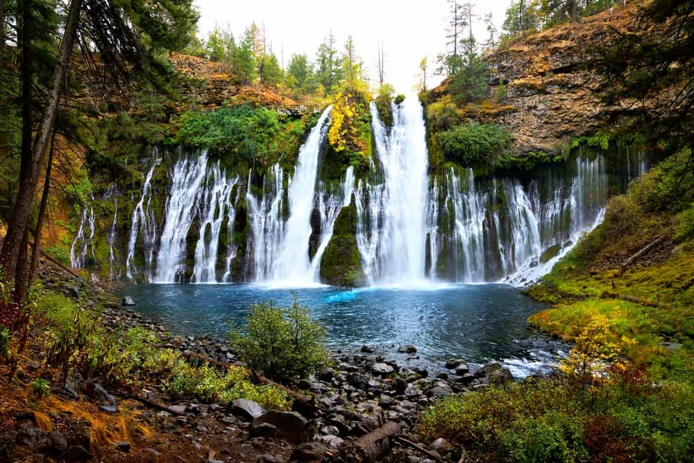 A cascading horseshoe-shape waterfall surrounded by autumn colored foliage all falling into a deep turquoise pool